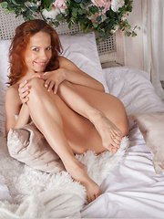 Dennie sensually poses on the bed baring her unshaven pussy.