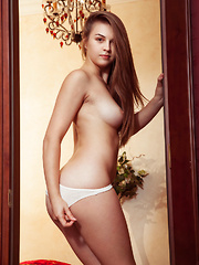 Bella Libre poses by the door baring her erect nipples and sweet pussy.