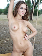Elina poses on the swing as she bares her sexy body and trimmed pussy.