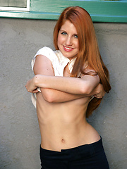 Long-legged redhead babe showing her young body