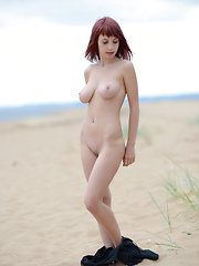 Wonderful busty redhead quean undressing and demonstrating enticing body on the seaside.