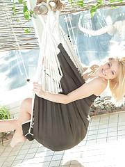 Wonderful blonde teen chick spreading shapely legs in a hammock hanging in the orangery.