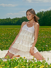 With her confident and elegant poses, Nastya youthful beauty stands out amidst a vast green field covered with tiny delicate flowers.