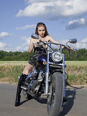 Wearing a sexy leather dress and boots Milena displays her petite and nubile body on top of a motorcycle - Erotic and nude girls pics at SoloTeenPics.com