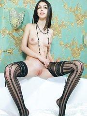 Flora C\'s long and slender physique accentuated by her black thigh-high fishnet stockings